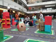 The tiny architects of Box City walk through the miniature buildings after learning about urban and city planning during the event sponsored by the American Institute of Architects. About 200 children designed and built the tiny buildings for the city, which took shape Saturday in the atrium of the Wellington E. Webb Municipal Building. (Jordan Steffen, The Denver Post)